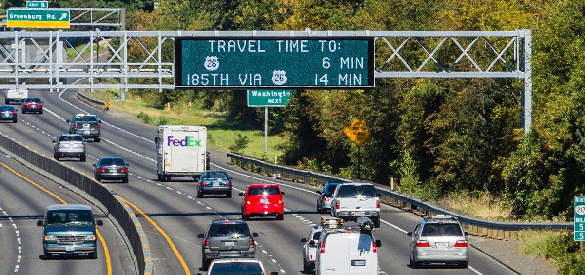Picture of cars on a freeway with a sign estimating travel time