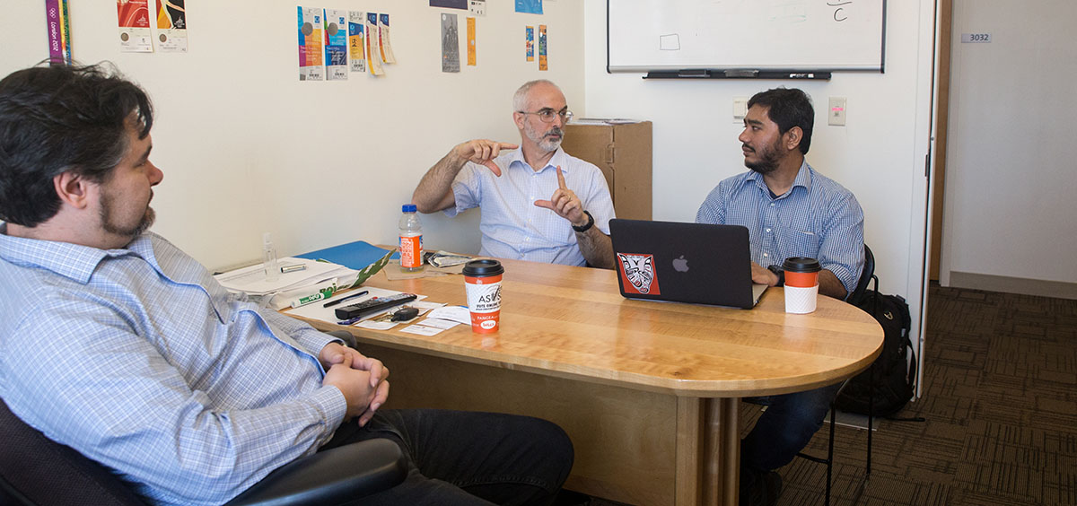 Photo of Carlos Jensen, Paul McKenney, and Iftekhar Ahmed talking in an office.