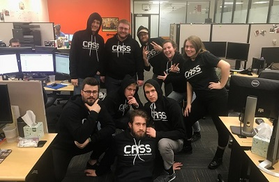 Photo of students in CASS t-shirts in office